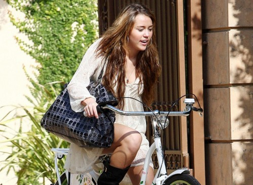 Miley Cyrus rides a bike