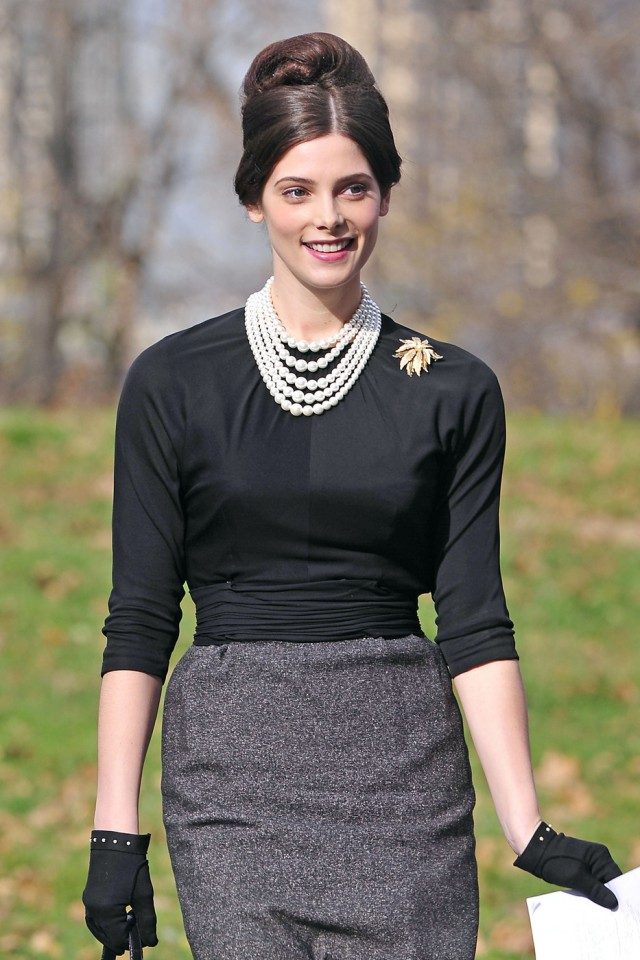 "Ashley Greene, wearing a pencil skirt and a neck full of pearls, holds onto a script as she prepares for her guest role on ""Pan Am"""